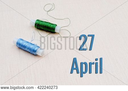 Handicraft Calendar 27 April. Skeins Of Green And Blue Threads For Embroidery On A Beige Background.