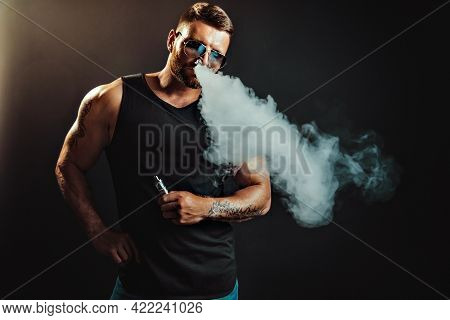 Bearded Brutal Male In Sunglasses Smoking A Vapor Cigarette As An Alternative To Tobacco. Studio Sho