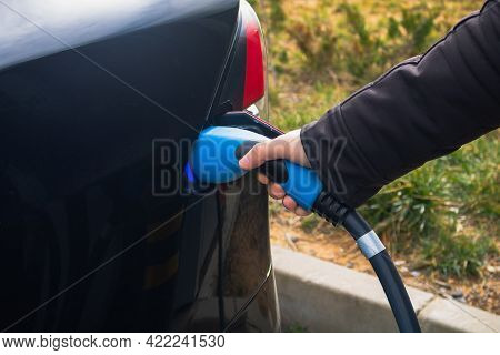 Man Holding An Attached Charger On The Electric Vehicle In Focus. High Quality Photo. Charging Ev Ca