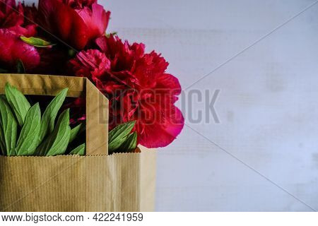 Bouquet Of Red Peonies In Shopping Bag Close-up On White Background. Top View. Copy Space. Holidays,