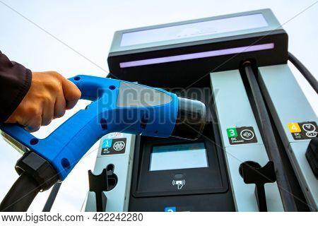 Man Holding A Ev Charger. Ev Charger Station On The Background. Ev Charger Station Background. Alter