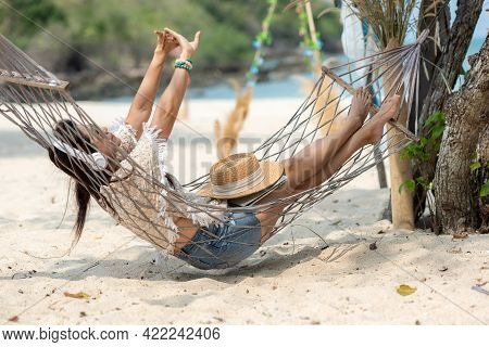 Lifestyle Freelance Woman Using Laptop Working And Relax On The Beach. Asian People On Hammock Succ