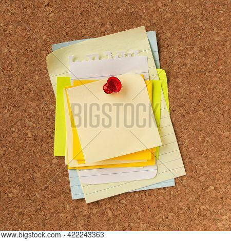 Pile of blank yellow notes stacked and pinned with a red tack. Empty copy space for important office notice, message, or reminder.