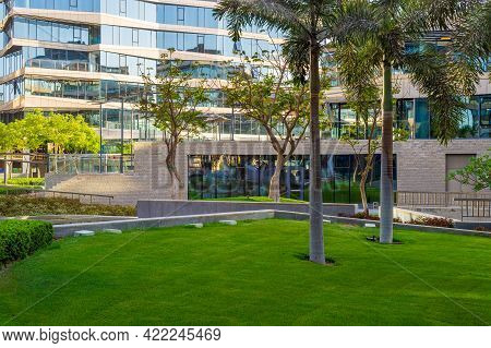 Contemporary Urban City District With Well Run Glass Building And Verdant Lawn And Trees On Sunny Da