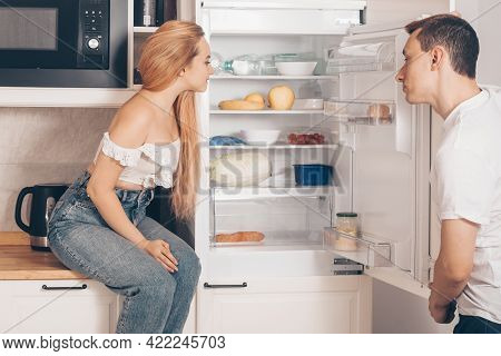 The Guy And The Girl In The Kitchen. Loving Couple At Home. The Couple Eats Healthy Food. Useful Rat