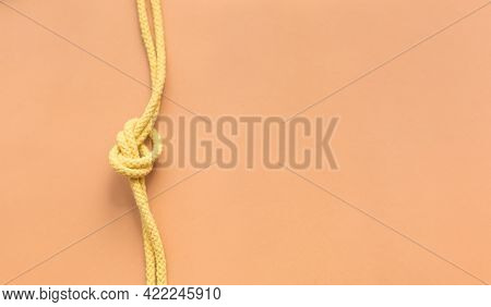 Yellow String Knotted On A Orange Colour Background