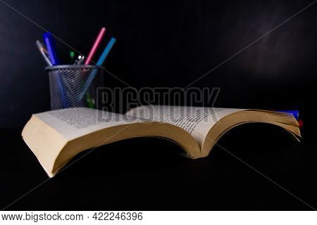An Opened Book With A Pen Stand In The Background And Blackboard Behind -graduation And Classroom Co