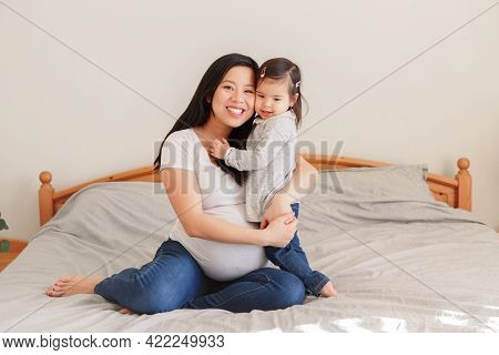 Asian Chinese Pregnant Woman With Toddler Girl Hugging On Bed At Home. Girl Daughter Kid Playing Wit