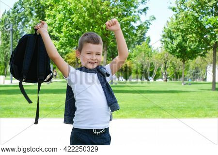 Schoolboy Rejoices At The End Of School. Up A Backpack, Jumping For Joy
