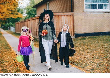 Trick Or Treat. Mother With Children Going To Trick Or Treat On Halloween Holiday. Mom With Kids Boy