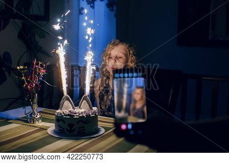 Parent Taking Photo Of Daughter Blolwing Candles On Birthday Cake. Using Smartphone For Taking Pictu