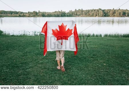 Girl Wrapped In Large Canadian Flag By Muskoka Lake In Nature. Canada Day Celebration Outdoor. Kid I