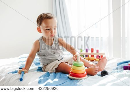 Cute Baby Toddler Playing With Learning Toy Pyramid Stacking Blocks At Home. Early Age Montessori Ed