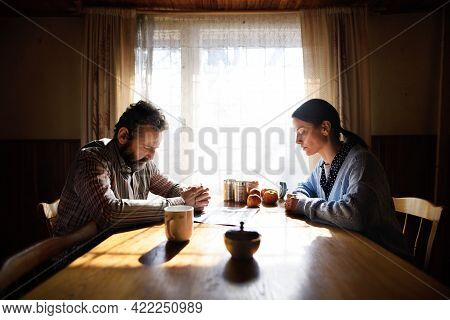 Portrait Of Sad Poor Mature Couple Praying At The Table Indoors At Home, Poverty Concept.
