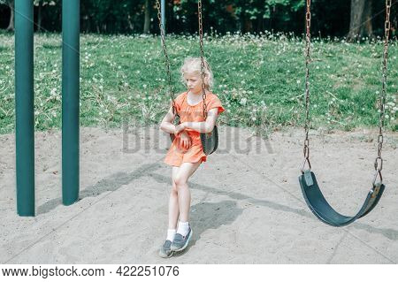 Sad Unhappy Girl Is Swinging On Swing Set In Park Outdoor Alone. Upset Bored Kid Waiting For Friend