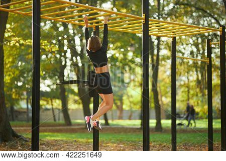 Back View Of Active Woman In Sport Clothing Crossing On Horizontal Bar During Outdoors Activity. Con