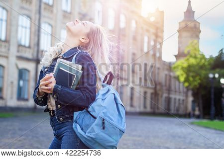 Attractive Female Student With Backpack Walking To Campus, Education Concept. Blonde Girl Is Smiling
