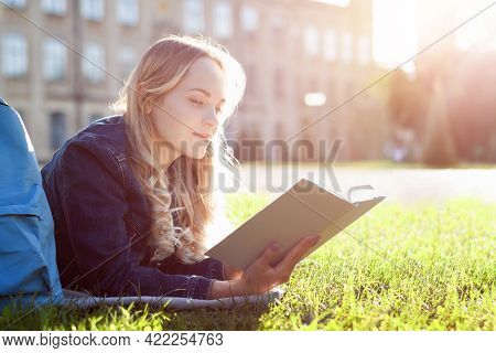 Young Woman Student Is Reading Book, Lying On Green Grass Yard Near College Building. Smart Blond Gi