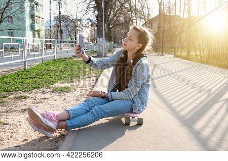 Beautiful Girl In Denim And Pink Sneakers With A Phone In Her Hand Sits On A Penny Board, A Longboar