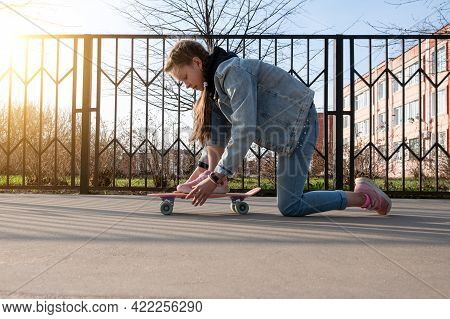Beautiful Girl In Denim Clothes And Pink Sneakers Does Exercises On A Penny Board, A Longboard. Inte