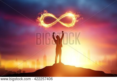 Infinity Fire Sign Over The Silhouette Of A Businessman On A Sunset Background
