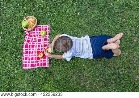 Little Boy Kid 5-6 Years Old Eats Apple Lying On Green Grass. Outdoors Picnic On Summer Sunny Day. T