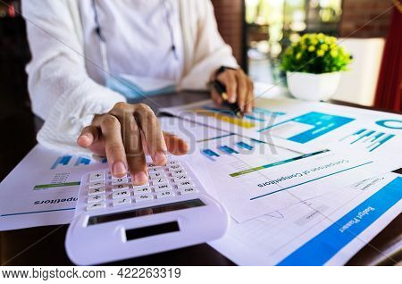 Close Up Businesswoman Hand Using A Calculator And Pointing Graph Report Document About Cost, Tax, P