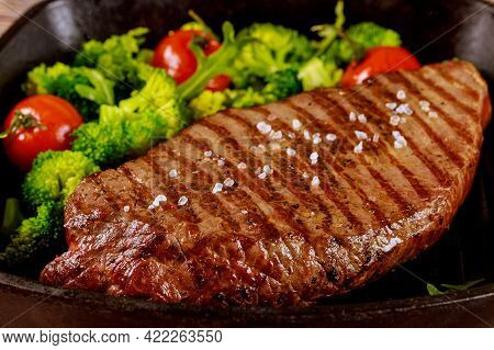 Grilled Medium Rare Beef Steak With Broccoli And Tomato On Grill Pan. Close Up.