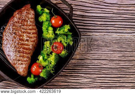 Grilled Rare Beef Steak With Broccoli And Tomato On Grill Pan On Wooden Background.