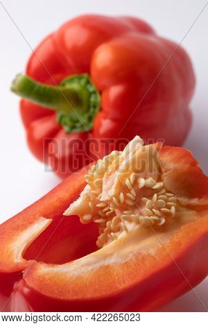 Whole and halved sweet red bell pepper with seed close up