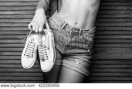 Girl With A Beautiful Figure In Jeans Shorts And White Shoes. Girl Hold A Pair Of Shoe. Woman Holdin