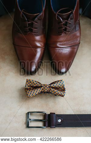 Brown Men's Shoes Made Of Genuine Leather, A Belt And A Bow Tie On A Beige Background, Close-up. Mor