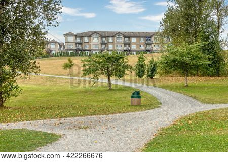 Gravel Pathway In A Park In Front Of Residential Building On The Hill