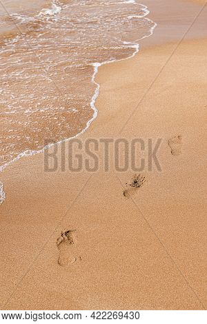 Bare Footprints At Sunset On Golden Beach Sand. Seashore, Wave And Footsteps In Sunlight. Beauty In