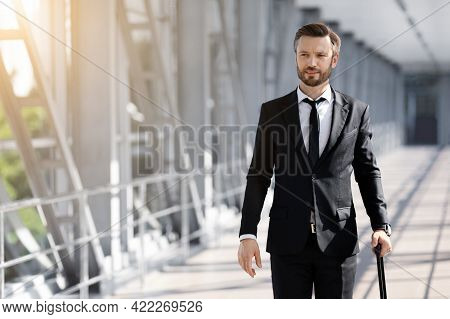Wealthy Businessman With Luggage Walking By Airport