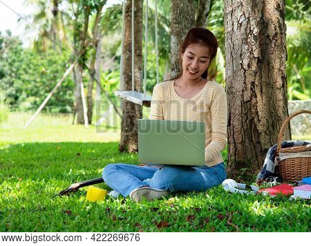 Asian Student Girl Is Studying  Online By Laptop In Garden. Asian Student Is Happy In Study Online.