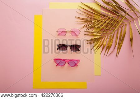 Stylish Sunglasses. Bright Summer Sunglasses On Pink Background With Gold Palm Leaves. Fashionable T