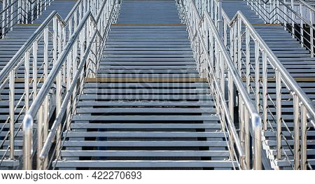A Staircase With Gray Concrete Steps And A Metal Railings Leading Up. An Element Of Urban Architectu