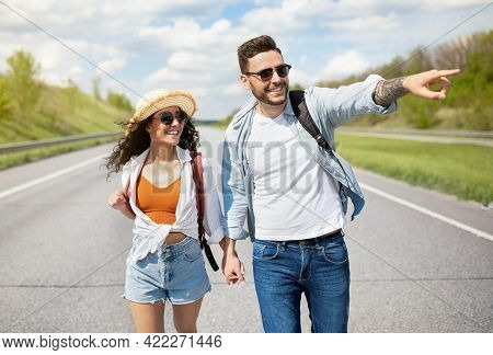 Cheerful Young Couple With Rucksacks Walking Along Road, Pointing Aside, Holding Hands, Hitchhiking