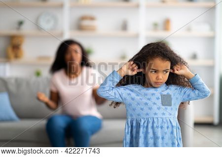 Family Argument. Sad Offended Black Girl Covering Ears, Not Wanting To Listen To Her Mothers Sclodin