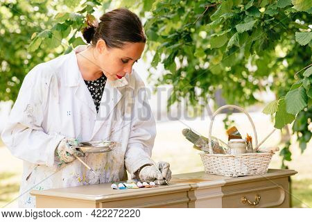 Young Latin Woman Restoring An Old Wooden Furniture. Restoration Of Antiques. Hispanic Person Workin