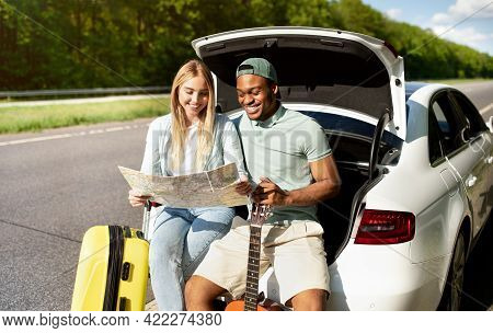 Multiracial Couple Going On Road Trip In Car, Looking At Map, Taking Break From Driving, Sitting In