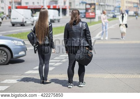 Two Pedestrian Girls Stand At A Pedestrian Crossing And Wait For A Traffic Light To Turn Green. View
