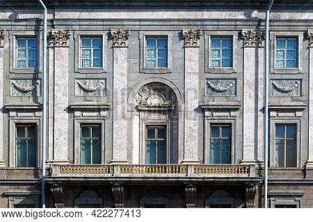 Facade Of The Building Is Clad In Marble With Windows And A Large Balcony With Gilded Balusters. Fro