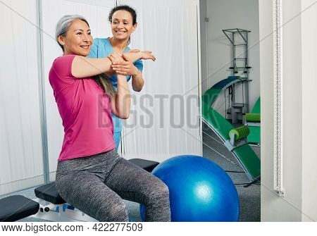 Mature Female Patient While Exercise Treatment With Her Physiotherapist. Rehab At A Medical Center