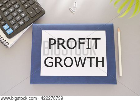 Profit Growth Text Written On White Paper Above On Notebook. Concept Of Business Success In Investme