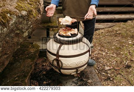 Cooking Meat On The Tandoor. Hands Hold A Grate With Poultry Meat