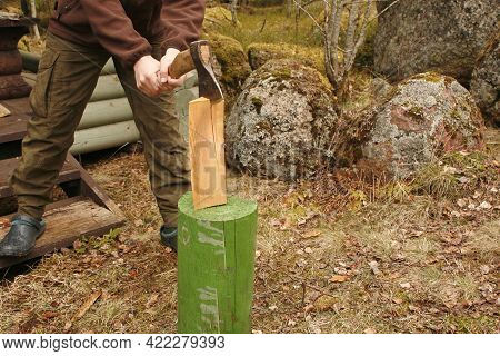 Hands With An Ax Chopping Wood. Young Man Chops Wood With An Ax In The Forest.