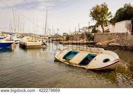 Old Wooden Fishing Boat Aground In Finikas Marina, Greece, With Sailing Boats In The Background.