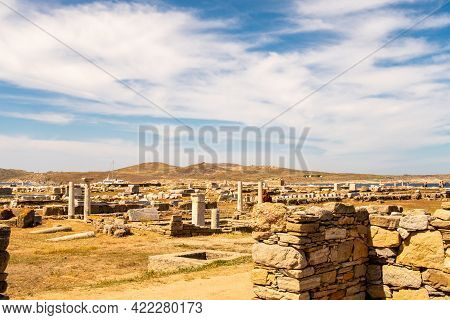 Landscape Of Delos Island In Greece - View From The Hill On The Island With Blue Cloudy Sky And Big